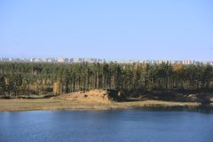 View of the beautiful forest lake and the house of a new building of the bigger city on the horizon.  royalty free stock image