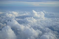 View of beautiful free form dense white cloud with shades of blue sky background from flying plane window Stock Photo