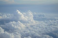 View of beautiful free form heaven white cloud with shades of blue sky background from flying plane window. In morning sunrise Royalty Free Stock Images