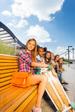 View of beautiful girls sitting on wooden bench Royalty Free Stock Photography