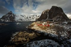 View of beautiful Hamnoya village in winter time with montains in background with light of sunrise. Lofoten, Norway stock photo