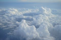 View of beautiful heaven cloudscape with shades of blue sky background from flying plane window. In morning sunrise Royalty Free Stock Images