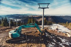 View of beautiful landscape of ski area being built, construction site with excavator and machinery on mountain slopes. Wide angle view of beautiful landscape of stock photos