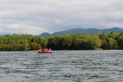 View of beautiful mountain river with tourists on orange raft on water royalty free stock photography