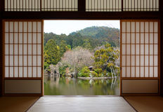 View of a beautiful oriental pond seen through open Japanese sliding doors royalty free stock photo