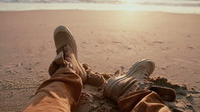 A view of a beautiful pastel sunset at the shore with a close up of two boots resting on the beach. stock video