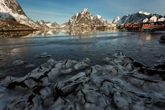View of beautiful Reine village in winter time with montains in background with light of sunrise. Lofoten, Norway stock images