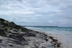 View of a beautiful rocky beach with white sand in Cuba. It´s a cloudy day and there are some waves in the ocean Royalty Free Stock Image