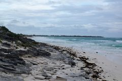 View of a beautiful rocky beach with white sand in Cuba. It´s a cloudy day and there are some waves in the ocean Stock Photography
