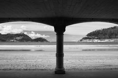 View on beautiful sandy beach la concha of san sebastian through arch arcade in black and white, basque country, spain. View on beautiful sandy beach la concha Stock Photography