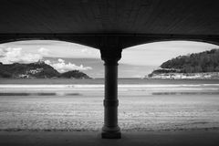 View on beautiful sandy beach la concha of san sebastian through arch arcade in black and white, basque country, spain. View on beautiful sandy beach la concha Royalty Free Stock Photo