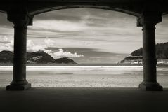 View on beautiful sandy beach la concha of san sebastian through arch arcade in black and white, basque country, spain. View on beautiful sandy beach la concha Royalty Free Stock Images