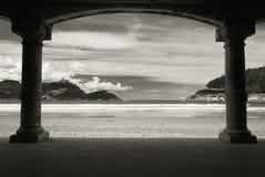 View on beautiful sandy beach la concha of san sebastian through arch arcade in black and white, basque country, spain. View on beautiful sandy beach la concha Stock Photos