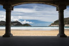 View on beautiful sandy beach la concha of san sebastian through under arch arcade, basque country, spain. View on beautiful sandy beach la concha of san Royalty Free Stock Images