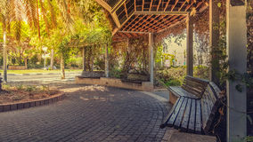 View of beautiful sidewalk pergola. Holon, Israel - May 26, 2016: Multi-entry semi-circular public pergola is surrounded by climbing lush green plants. There are Stock Photography