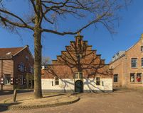 View of a beautiful stepped gable house in a Dutch village, photographed in early spring, the first spring day, with trees that st Royalty Free Stock Photos