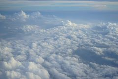 View of beautiful wide wonderland cloudscape with shades of blue sky background from flying plane window Royalty Free Stock Photos