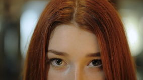 It is a view of beautiful young woman eyes of green color sitting in front of care inside. With bright lights around her. Her eyes are winking charming and cute stock video footage