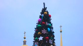 View of beautifully decorated tall Christmas tree against church, sequence. Stock footage stock video
