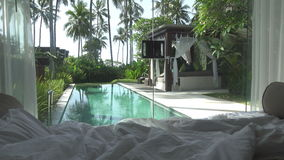 View from the bedroom on pool and a tropical garden with palm trees stock video footage