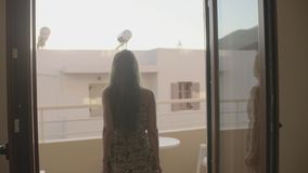 Woman in a Hotel. View from behind of beautiful woman stands on the balcony or terrace in apartment at morning time.Young lady enjoying the sun on the balcony of stock video footage