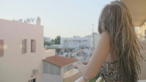 Woman in a Hotel. View from behind of beautiful woman stands on the balcony or terrace in apartment at morning time.Young lady enjoying the sun on the balcony of stock footage