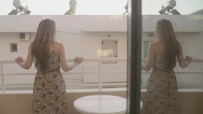 Woman in a Hotel. View from behind of beautiful woman stands on the balcony or terrace in apartment at morning time.Young lady enjoying the sun on the balcony of stock video