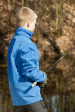 View from behind of boy with fishing rod Stock Photography