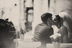 A view from behind on the bride and groom kissing in the street- Royalty Free Stock Image