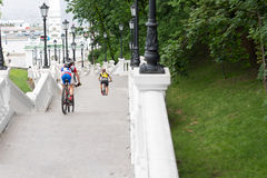 View from behind of cyclists descending steps. View from behind of cyclists descending a long flight of stairs past leafy green trees towards a river or waterway Stock Image