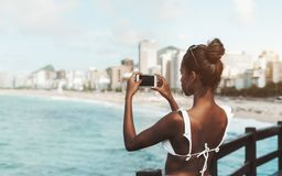 African-American girl taking pics of the coast using her cellphone royalty free stock photo