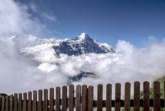 View from behind the fence to the Eiger mountain surrounded by clouds. stock photos