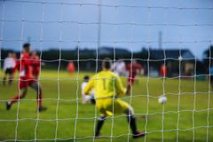 View from behind a footbal goal where the players are out of focus. And the net in focus stock photo