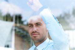 View from behind glass.businessman looking out the window of the office. royalty free stock photography