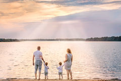 View from behind of happy family watching the sunset and sailboa. View from behind of happy family from mother, father and two boys watching the sunset and Stock Image