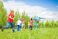 View from behind of kids running through field stock photography