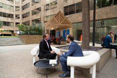 Two adult men sitting in a designer chair talk about work in a outdoor cafe stock photography