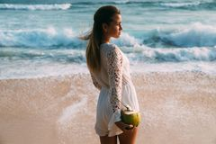 View from behind portrait of a girl with a coconut in her hand, and a straw. The European in fashionable beach clothes Royalty Free Stock Image