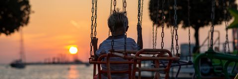 View from behind of a toddler boy riding on a carousel by the sea stock image