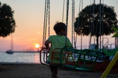 View from behind of a toddler boy riding on carousel by the sea stock image