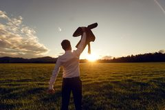 View from behind of a young businessman standing in beautiful field. Lit by the setting sun raising his suit jacket high up in the air in triumph stock image