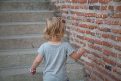 View from behind of a young girl climbing up stairs Royalty Free Stock Photography