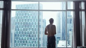View from behind of young man in shorts looking out at view of the city. View from the window shows skyline with iconic royalty free stock photography
