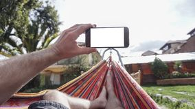 View from behind a young woman lying in a hammock and looking at smartphone. A View from behind a young woman lying in a hammock and looking at smartphone Royalty Free Stock Photo