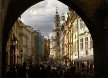 View of the bell tower of the church of St. Nicholas from the arch of the Charles Bridge in Prague. View of the bell tower of St.Nicholas Church from the arch of Royalty Free Stock Image