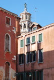 View of a bell tower and houses in Venice. Stock Photos