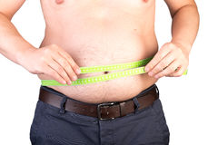 View of a the belly of a overweighted male scaling his waist wit. H a measuring tape - isolated on white background Stock Photos
