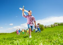 View from below of boy with toy and kids running Stock Images