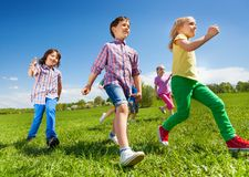 View from below of children running in the park. View from below of children running in the green park during daytime and sunny beautiful weather Stock Photo