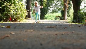 View from below on a girl skateboarding. Sunny autumn day in park, outdoor activity. stock video footage